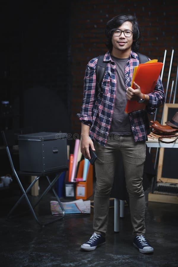 站立和拿着在Warehous里面的亚裔大学生书 图库摄影