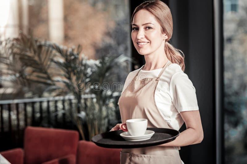 站立和拿着有一杯咖啡的美丽的女服务员一个盘子 免版税库存照片