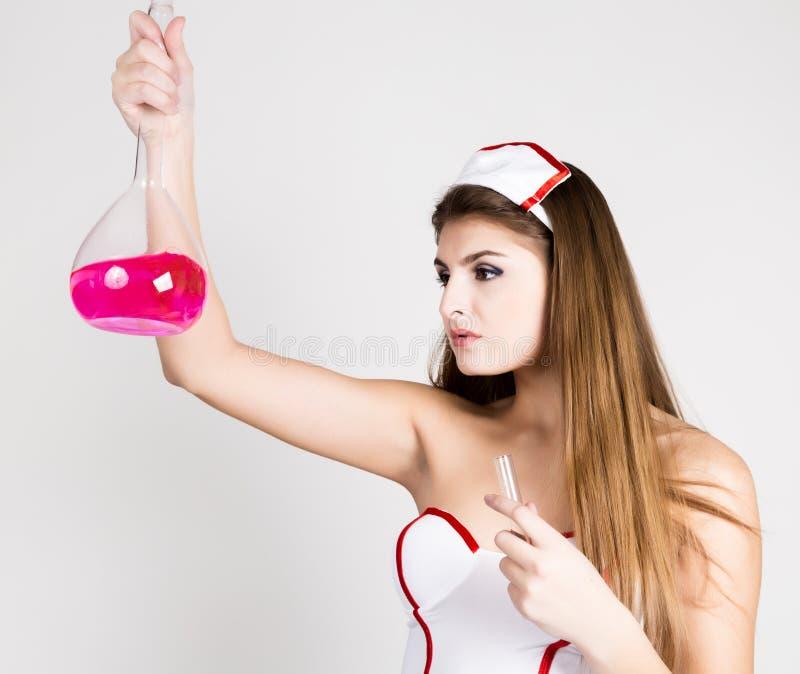 站立和拿着有桃红色液体的美丽的微笑的性感的护士试管