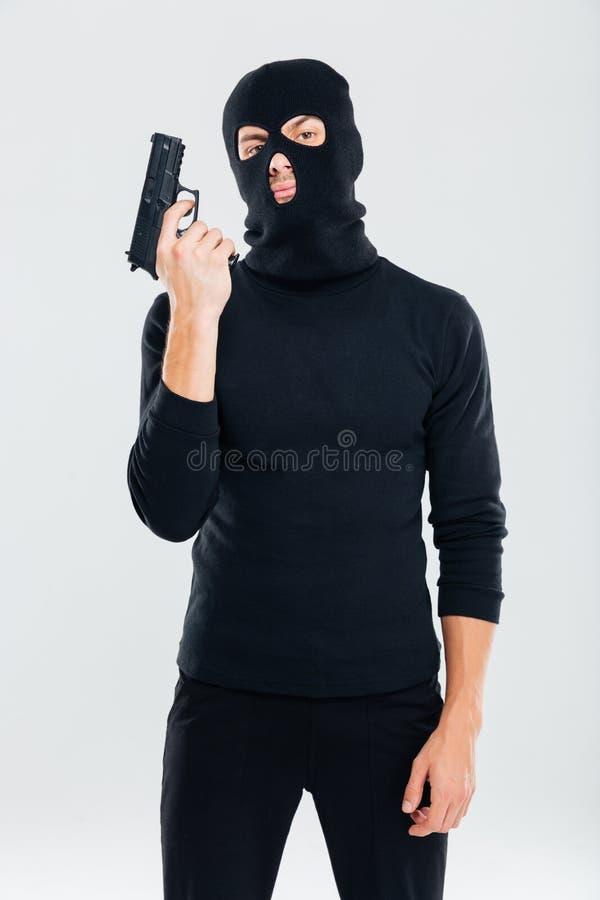 站立和拿着枪的巴拉克拉法帽的犯罪人 免版税库存图片