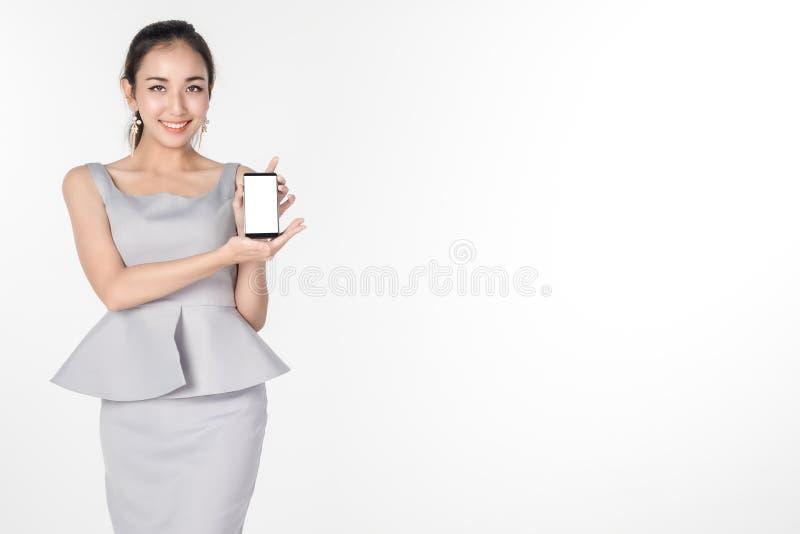 站立和拿着礼物的确信的年轻女商人黑屏数字式片剂某事在白色 库存图片