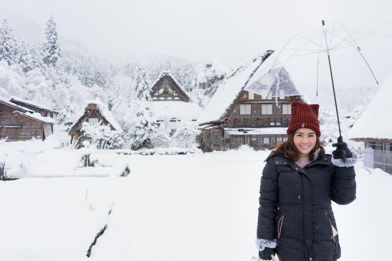 站立和拿着透明伞在冬天和雪的妇女跌倒 有积雪的村庄背景  库存图片