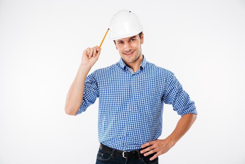 站立和拿着铅笔的安全帽的快乐的人建筑师 免版税库存图片