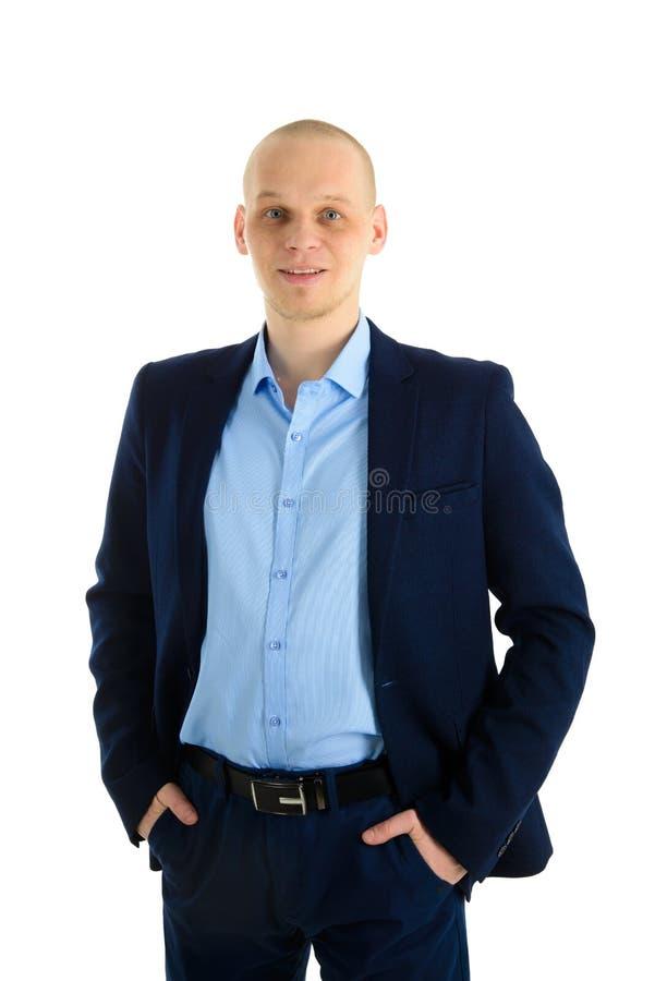 站立和握在口袋的蓝色衣服的激动的英俊的白种人人手,隔绝在白色背景 免版税图库摄影