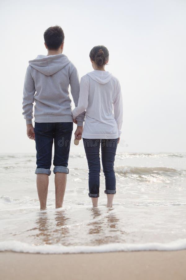 站立和握在海滩的手和看对海的年轻夫妇 免版税库存图片