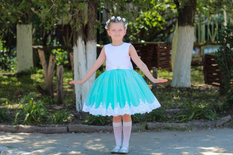 站立和摆在自然背景,有人造花花圈的孩子的礼服的美丽的小女孩在她的头的 免版税图库摄影