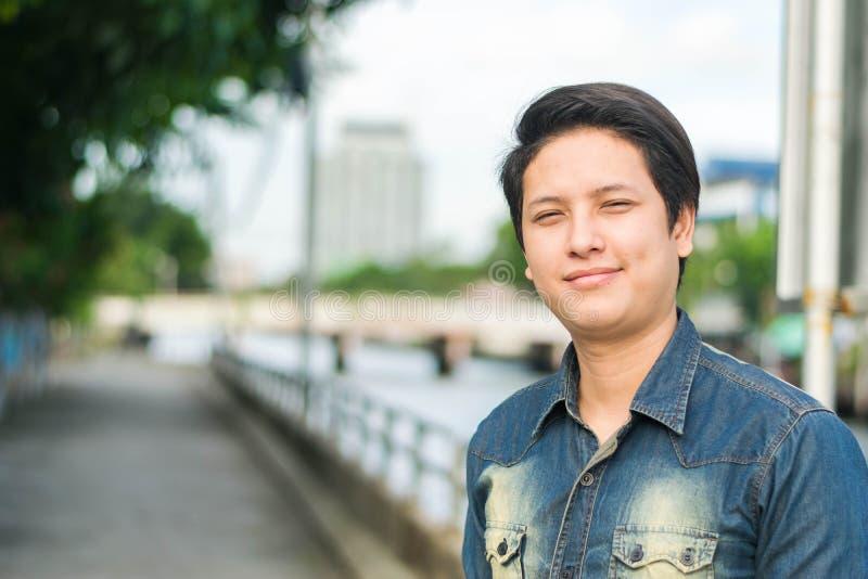站立和显示他愉快微笑的亚裔人 免版税库存图片