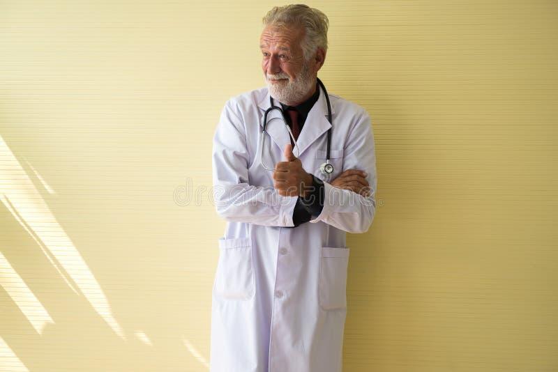 站立和显示赞许的资深医生画象在医院,愉快和微笑的正面想法的态度,复制te的空间 图库摄影
