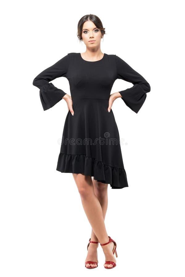 站立和看与胳膊的黑装饰衣裙礼服的迷人的拉丁妇女照相机在臀部 免版税图库摄影