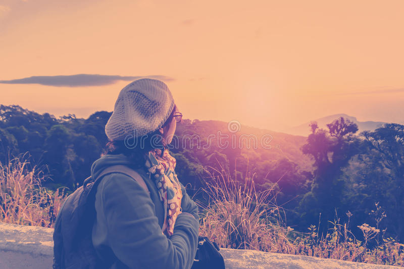 站立和看早晨阳光的女性游人 免版税库存图片