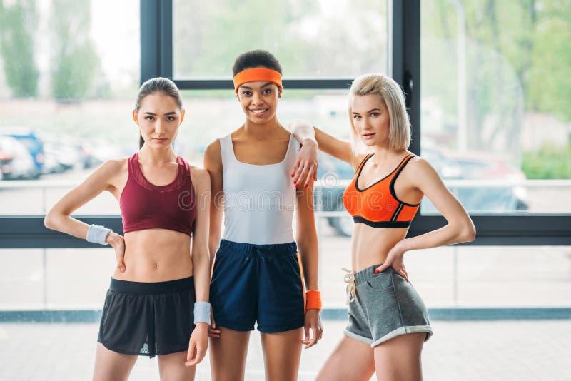 站立和看照相机的三个多文化女运动员 免版税图库摄影