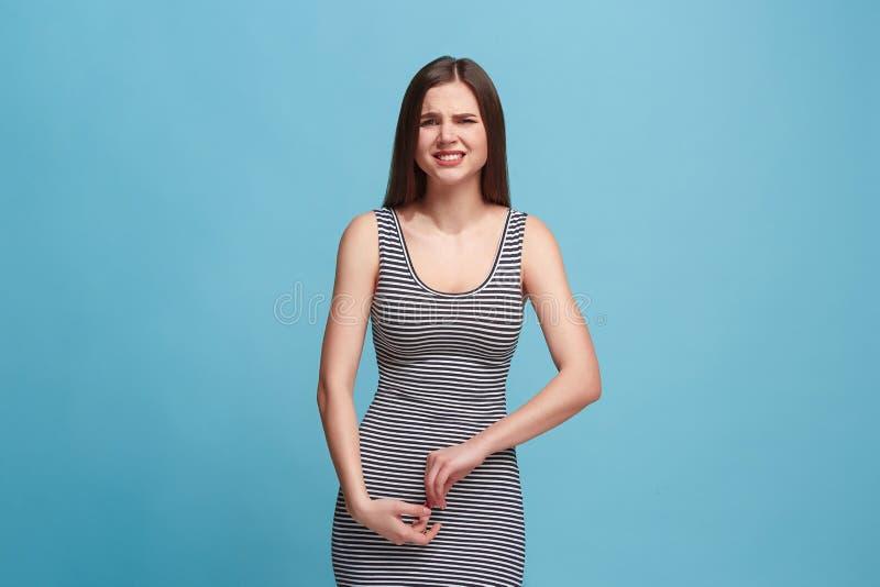 站立和看照相机的笨拙妇女反对蓝色背景 免版税库存照片