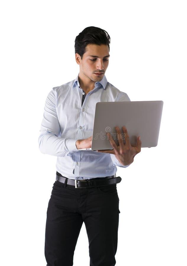 站立和研究便携式计算机的年轻人 库存图片