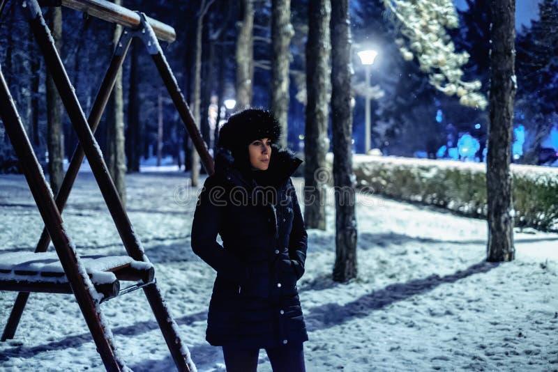 站立和认为在公园的女孩盖在雪 免版税库存图片