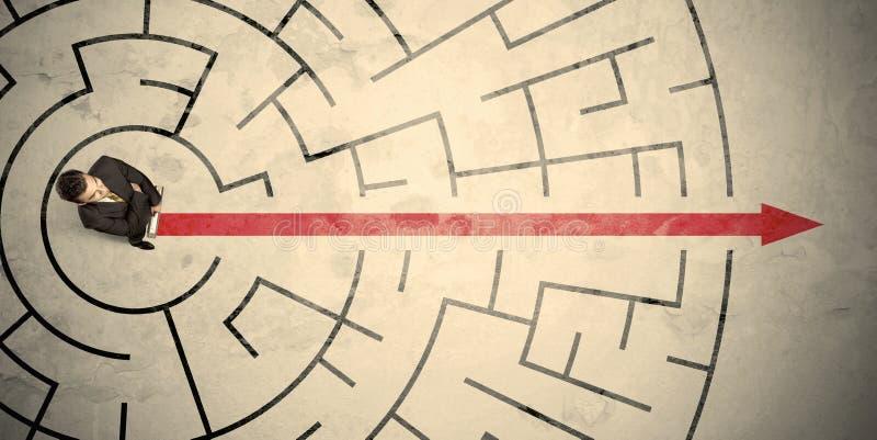 站立在一个圆迷宫中间的企业人 库存照片