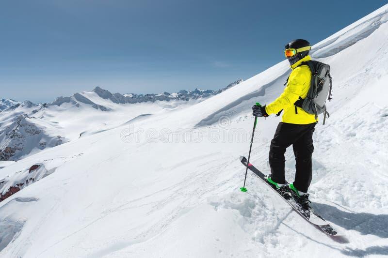 站立在一个多雪的倾斜的一个专业讨便宜者的滑雪者的画象以积雪覆盖的山为背景 免版税库存图片