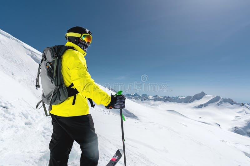 站立在一个多雪的倾斜的一个专业讨便宜者的滑雪者的画象以积雪覆盖的山为背景 图库摄影