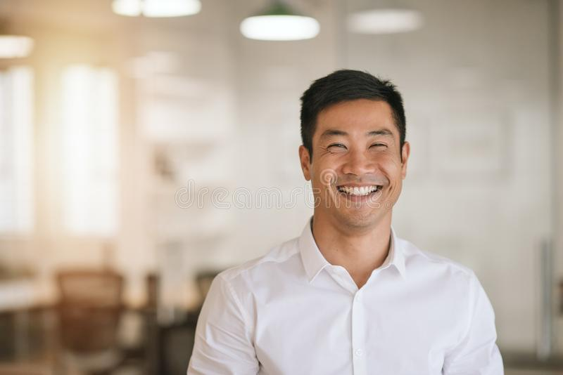 站立在一个明亮的现代办公室的微笑的亚洲商人 免版税库存图片
