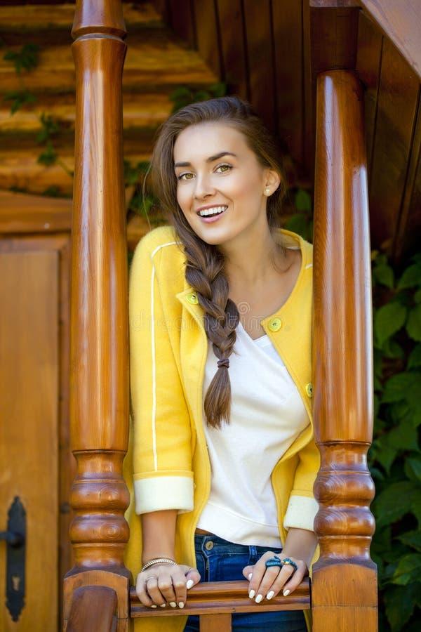 站立在一个木房子的门廊的愉快的少妇 图库摄影