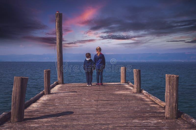 站立在一个木码头的兄弟姐妹 免版税库存图片