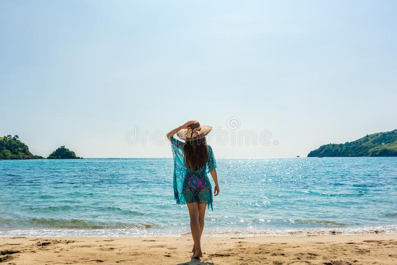 站立在一个热带海滩的年轻人适合的妇女在暑假 免版税库存照片