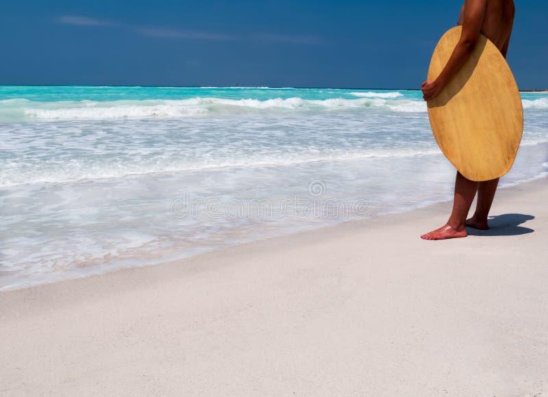 站立在一个热带海滩的冲浪者 免版税图库摄影