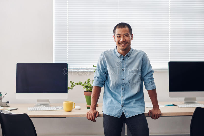 站立在一个现代办公室的微笑的年轻亚裔设计师 图库摄影