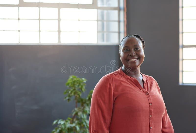 站立在一个现代办公室的确信的年轻非洲女实业家 库存图片