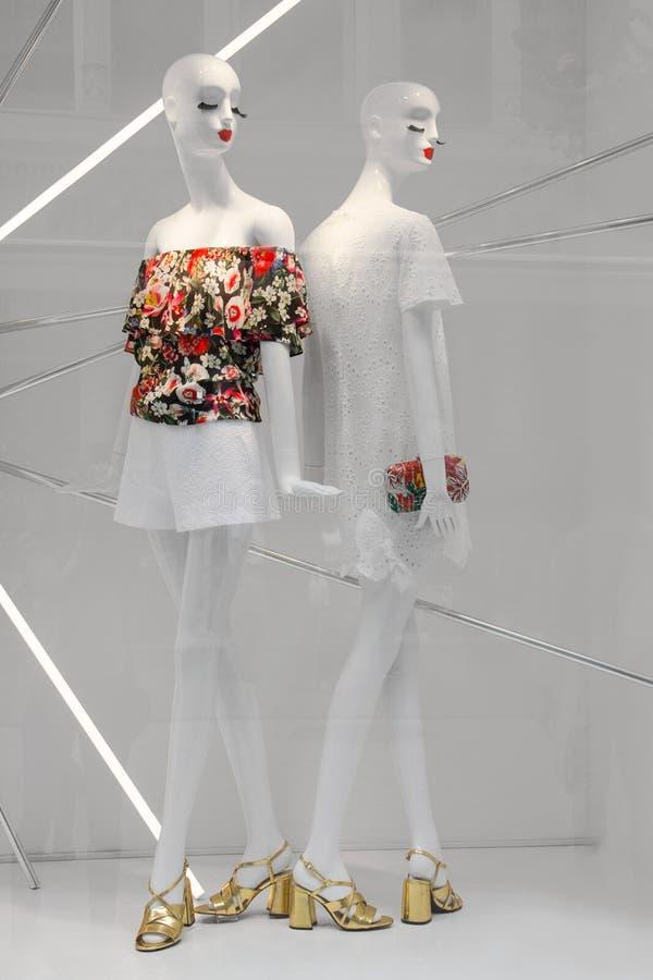 站立在一个现代商店窗口里的两个白色时装模特 免版税库存图片