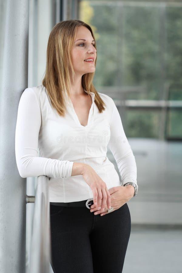 站立在一个现代大厦的女实业家 免版税图库摄影