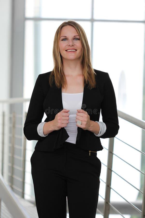 站立在一个现代大厦的女实业家 库存图片