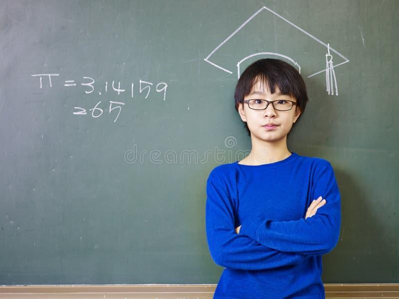 站立在一个白垩被画的博士盖帽下的亚裔男小学生 免版税库存图片