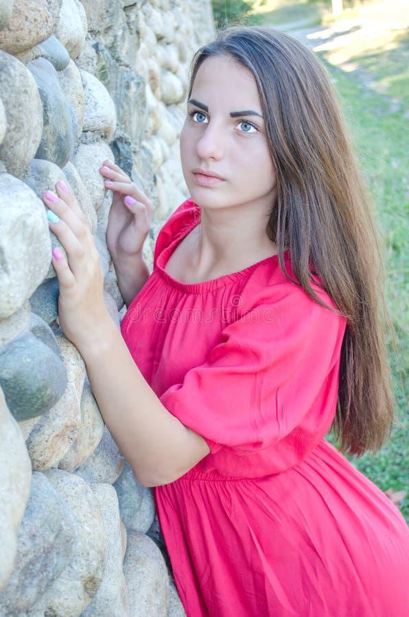 站立在一个石墙附近的女孩 库存照片
