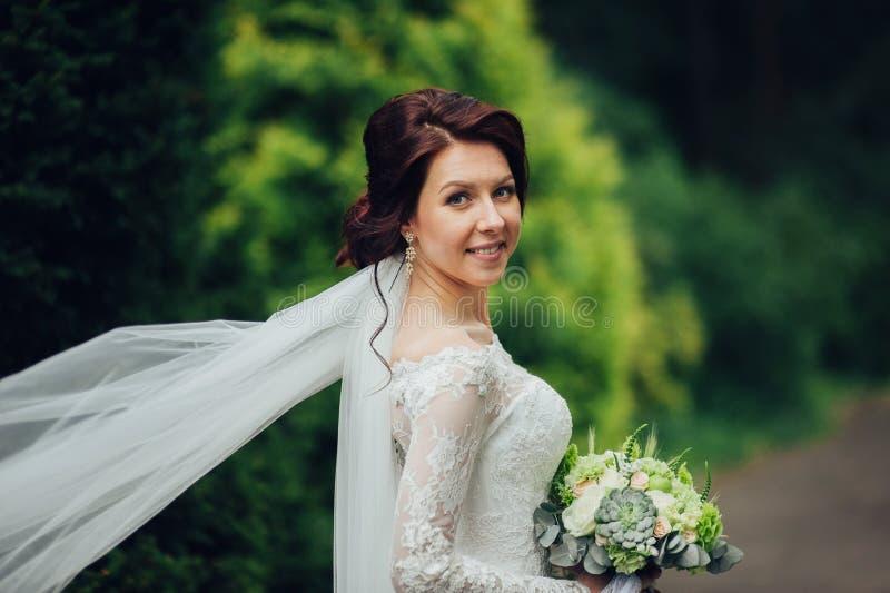 站立在一个绿色庭院里和拿着weddin的礼服的新娘 免版税库存图片