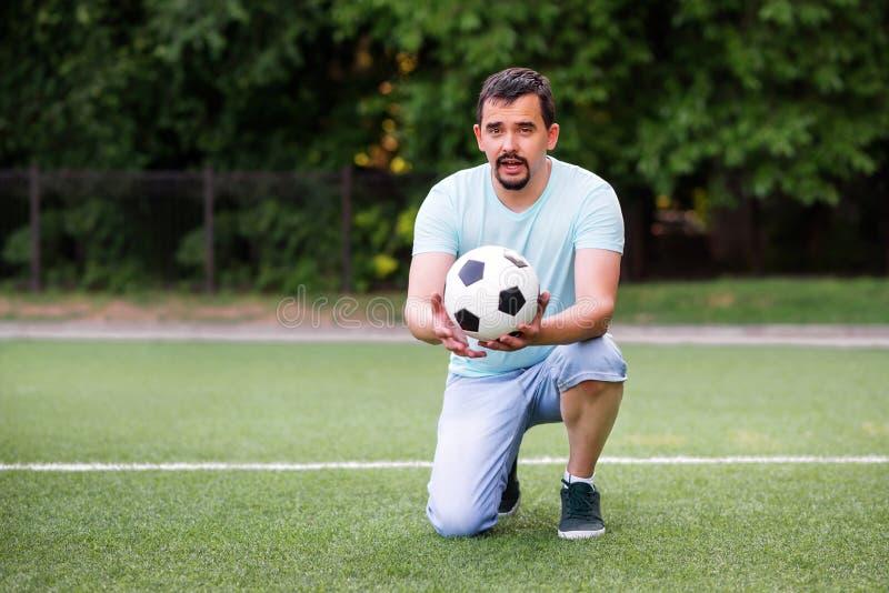 站立在一个膝盖的足球教练或体育教师画象拿着和给足球照相机和谈话在绿色领域 库存照片