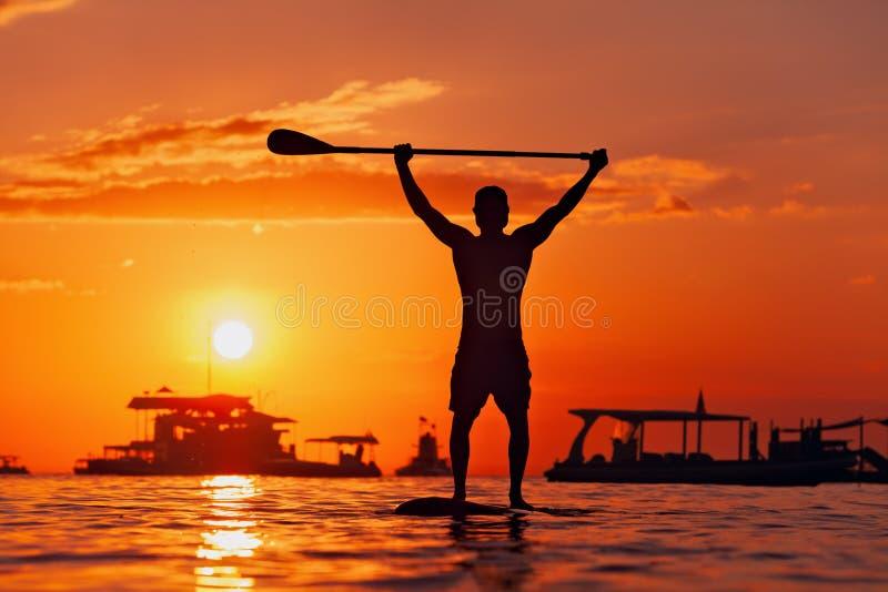 站立在一口的桨房客黑日落剪影 免版税库存照片