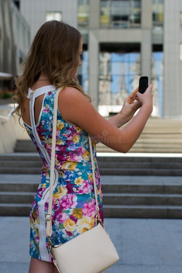 站立在一城市的街道上的美丽的女孩 免版税库存照片