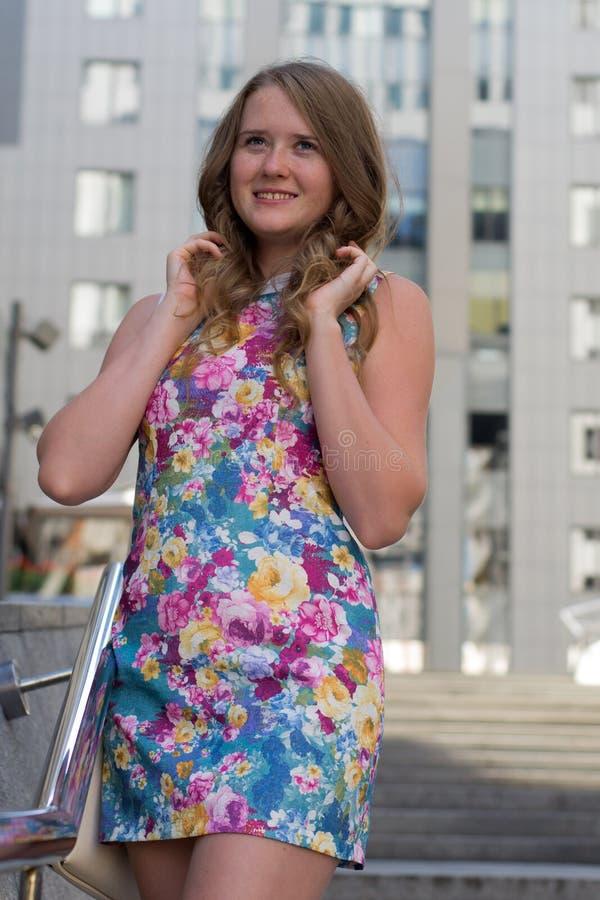站立在一城市的街道上的美丽的女孩 免版税图库摄影