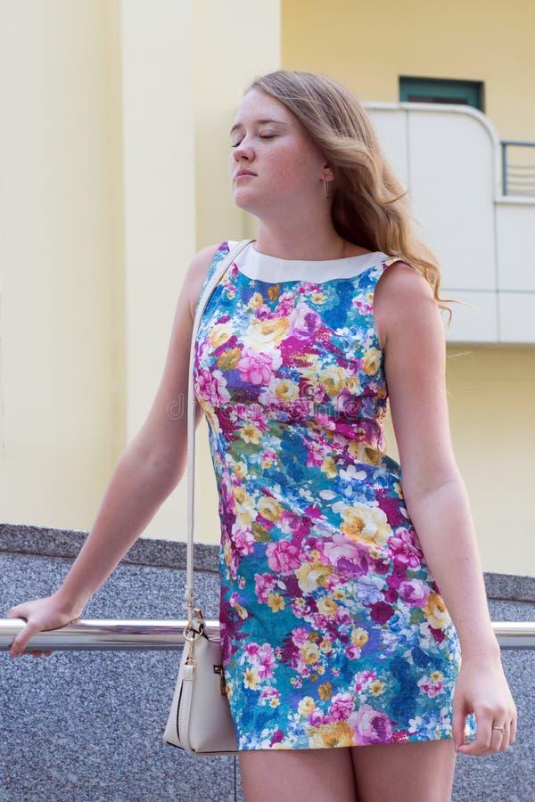 站立在一城市的街道上的美丽的女孩 免版税库存图片