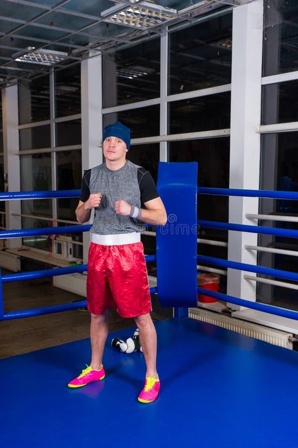 站立在一座规则拳击台的运动男性拳击手 库存图片