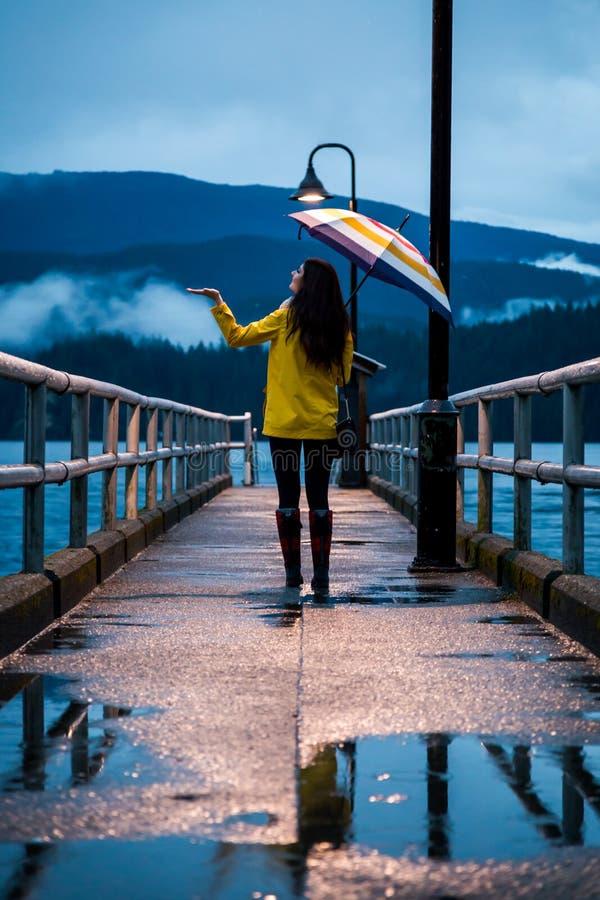 站立在一把伞下的一件黄色雨衣的少妇在一个雨天在海洋旁边 库存照片