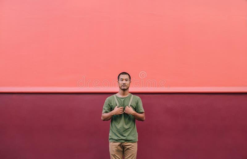 站立在一条五颜六色的城市街道上的凉快的年轻亚裔人 免版税库存照片
