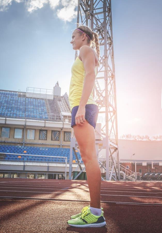 站立在一条红色连续轨道的女运动员佩带的T恤杉和短裤在竞技体育场内 免版税库存图片