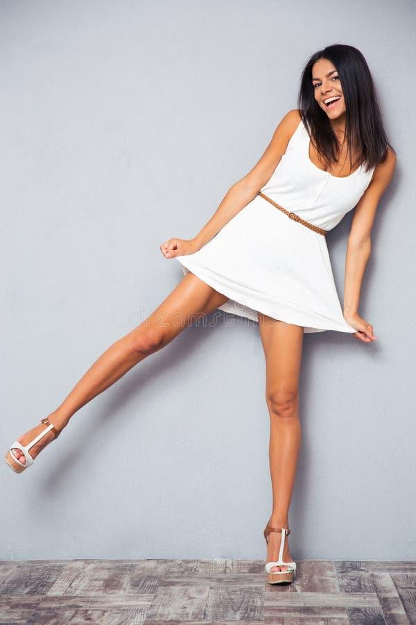 站立在一条腿的滑稽的愉快的妇女 图库摄影