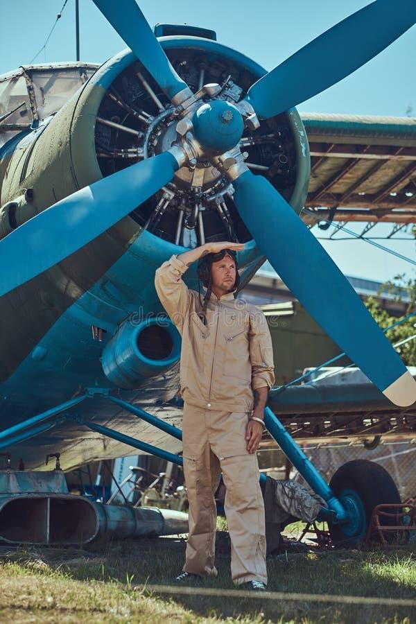 站立在一架减速火箭的军用飞机和神色附近的一个充分的飞行齿轮的英勇英俊的飞行员  库存图片
