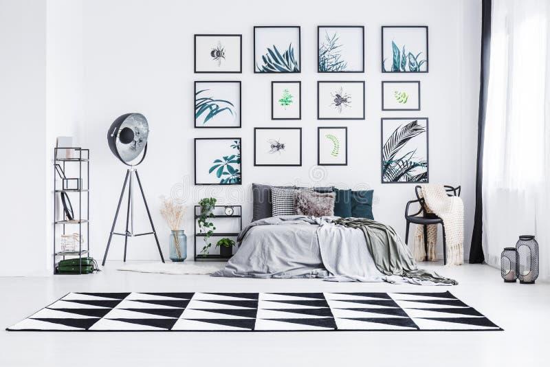 站立在一盏灯和一把椅子之间的床的真正的照片在bri 免版税库存图片
