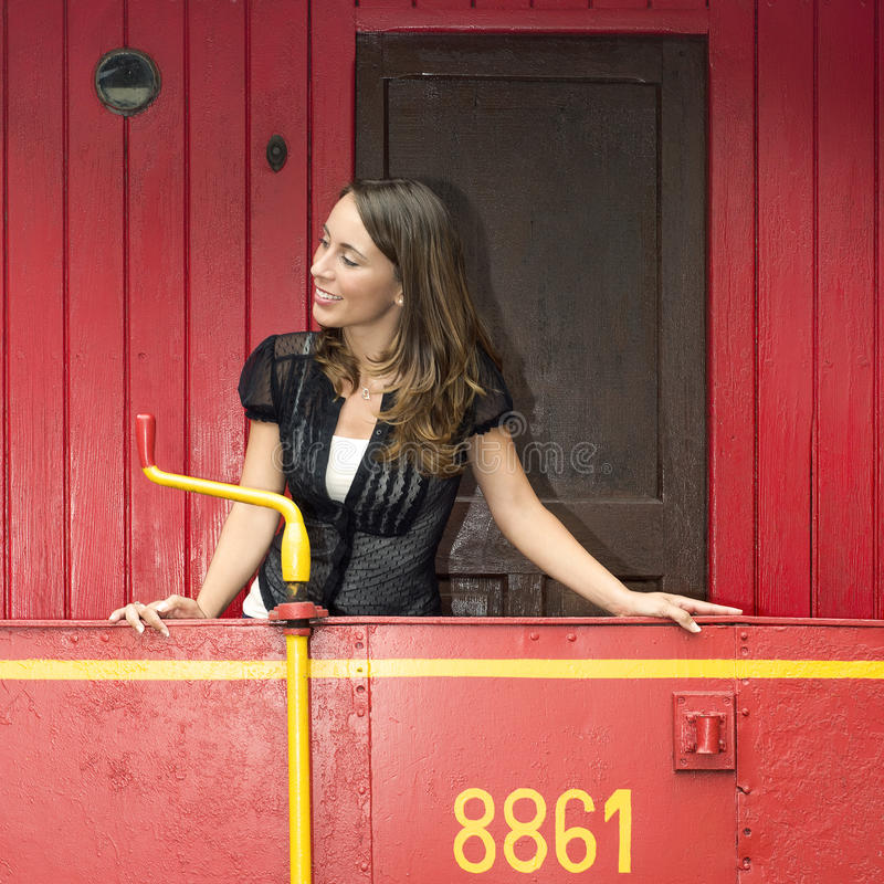 站立在一辆红色守车的妇女 库存图片