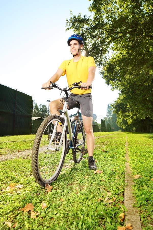 站立在一辆自行车的黄色衬衣的年轻人在公园 免版税库存照片