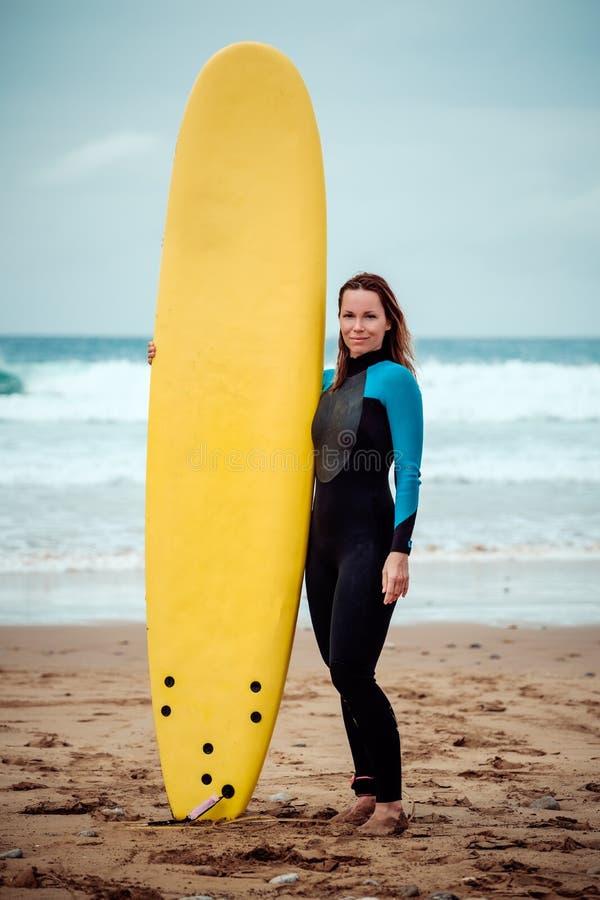 站立在与冲浪板的海滩的冲浪者妇女佩带的保温潜水服 库存图片