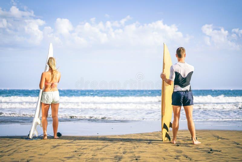 站立在与准备的冲浪板的海滩的冲浪者年轻夫妇冲浪在高波浪-获得健康的朋友乐趣 免版税库存照片